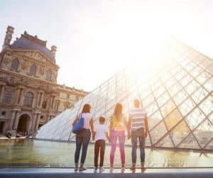Fun Virtual Museum Tours For Kids.  Family Looking at Glass Pyramid in the Courtyard of the Louvre Museum.
