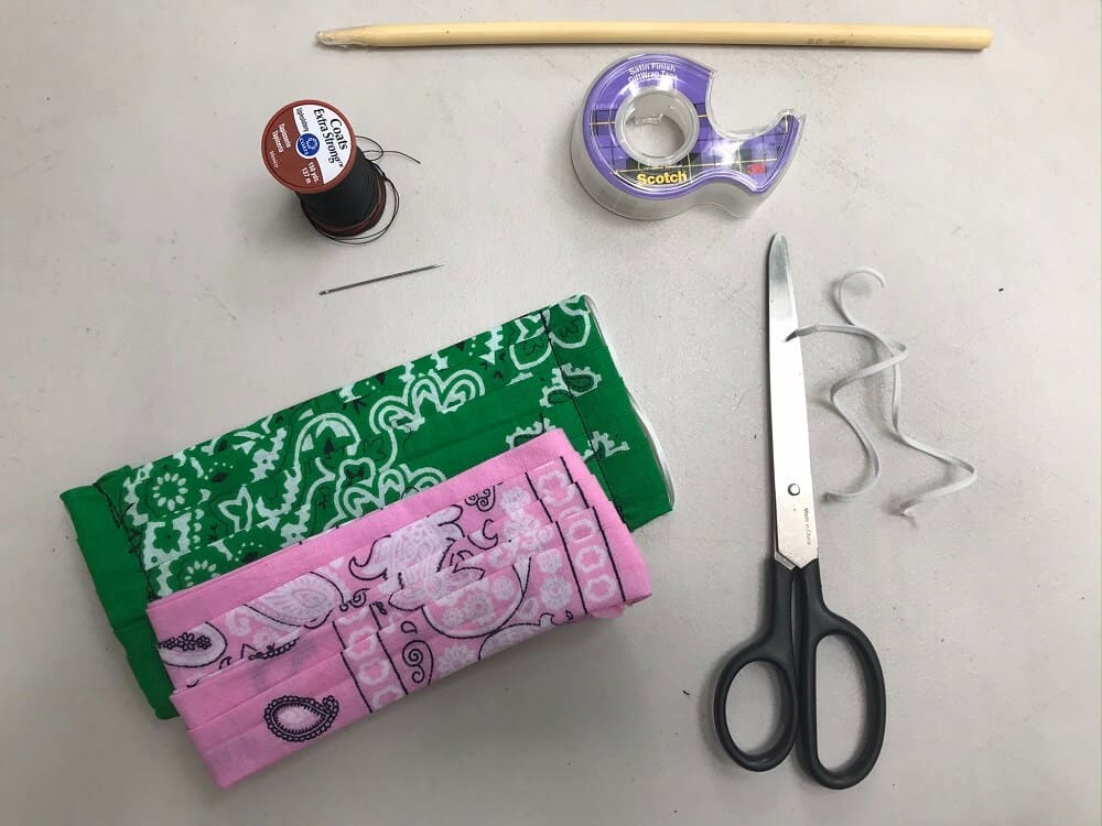 Bandana Face Mask Supplies including bandana, needle and spool of thread, scotch tape, wooden knitting needle, pair of scissors with black handle, and two elastic strips on white background