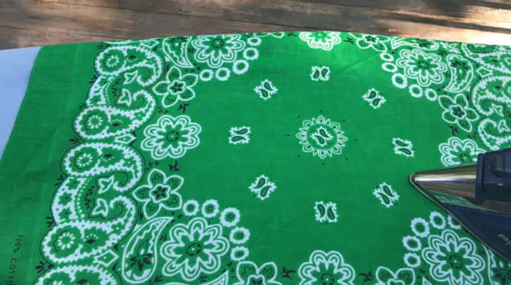 Green bandana laid out on blue ironing board with iron placed on it in lower right corner