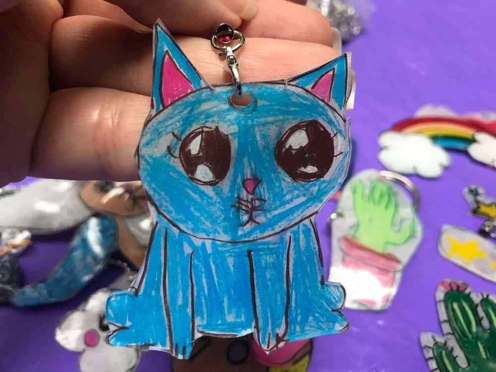 Close up of blue cat shrink dink with hook accessory held by a hand with shrinky dinks on a purple table top in the background