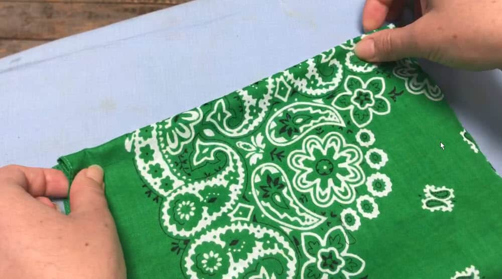 two hands bringing both sides of the green bandana face mask together on a blue ironing board