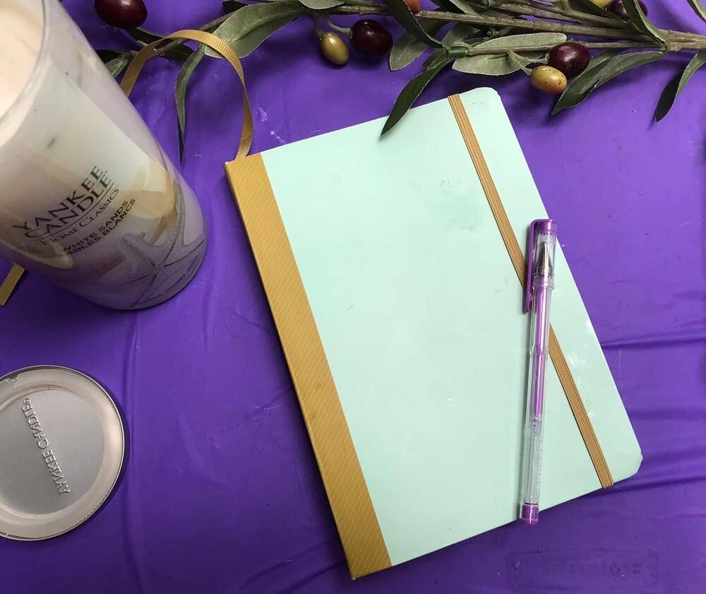 Bullet Journal with Purple Pen on Top Olive Branch and White Candle
