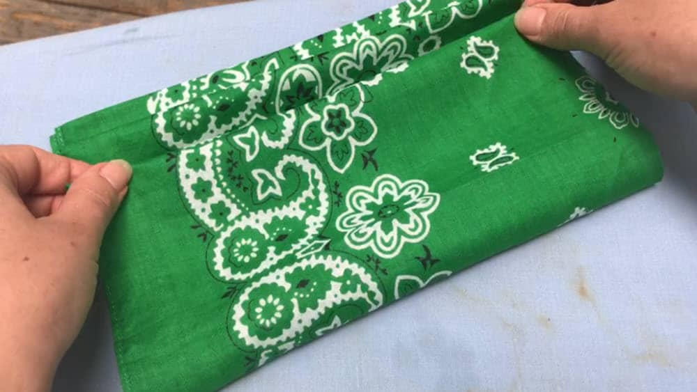 two hands continuing to cinch the top layer of green bandana mask on blue ironing board