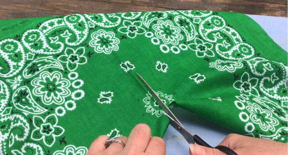 Two female hands holding scissor cutting a green bandana down the middle that is on top of a blue ironing board