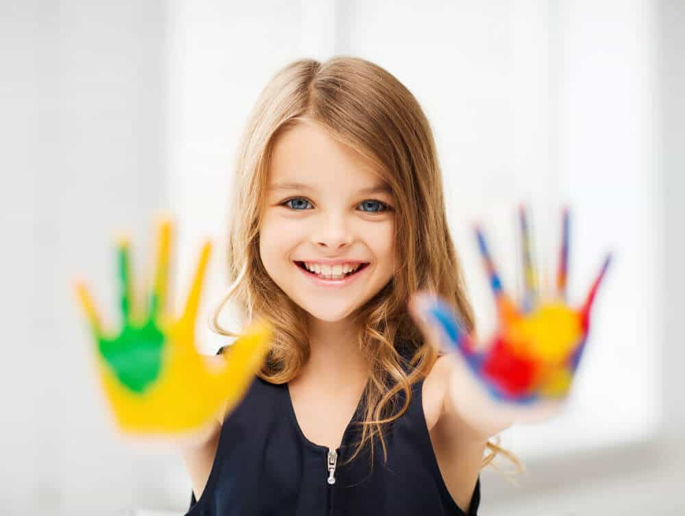 little girl with blond hair smiling and putting her arms out and palms up to show the colorful paint on her hands