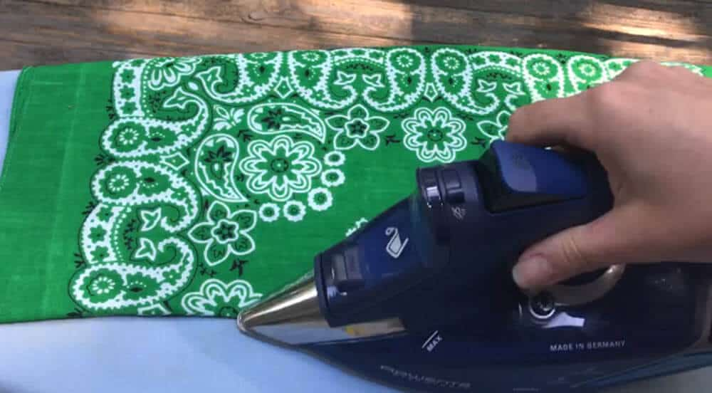 Green bandana folded in half on an ironing board and being pressed by an iron on top of a blue colored ironing board
