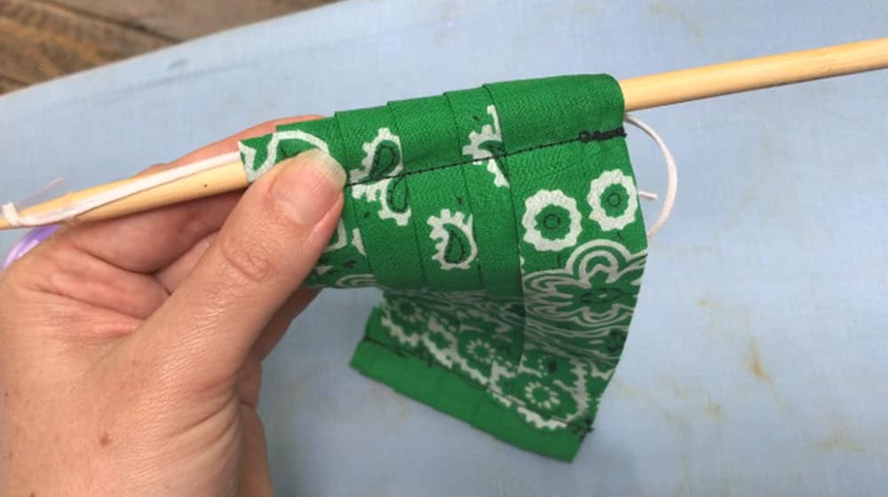 hand holding green bandana face mask with elastic strip taped to a wooden knitting needle pulled through the seam
