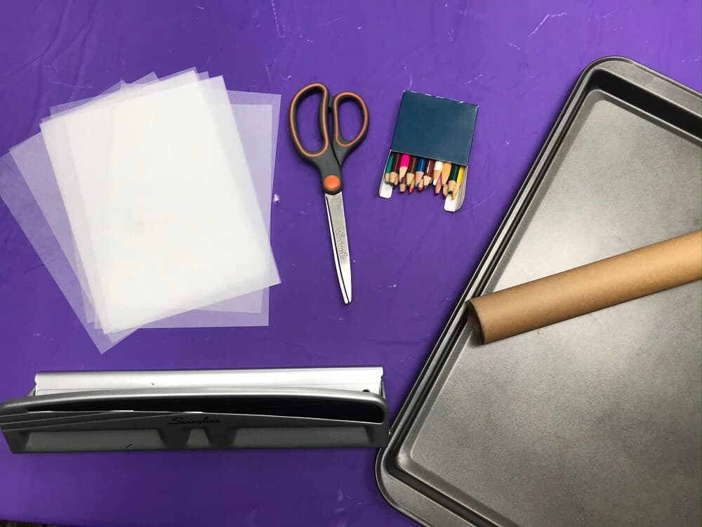 Supplies Needed for Easy and Fun Shrinky Dinks - Shrinky dink paper, hole puncher, scissors, box of color pencils, baking sheet, and roll of parchment paper on a purple background