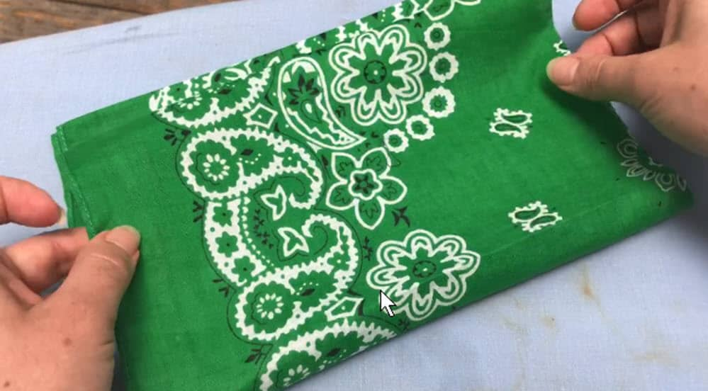 two hands grabbing material for green bandana to make cinches