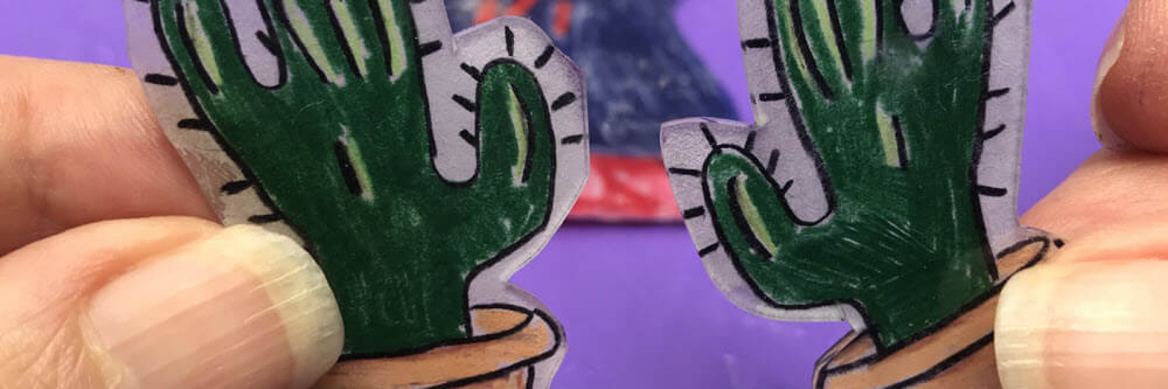 Close Up of Two Green Cactus Shrinky Dinks being held by finges with a purple background