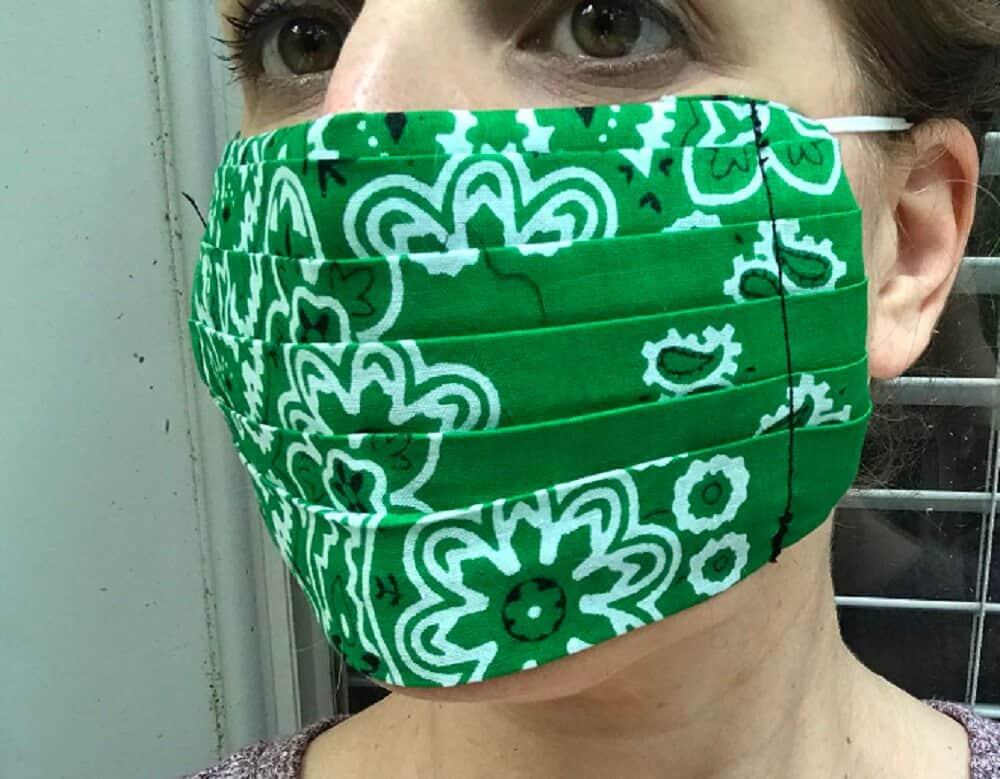 close up of woman wearing finished green bandana face mask