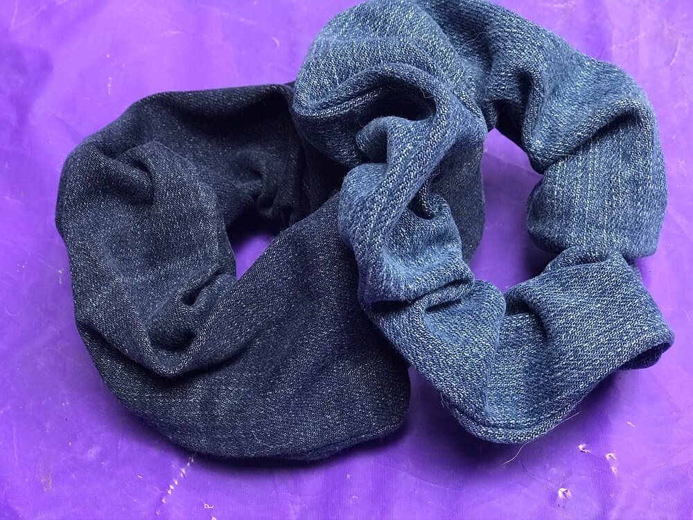 close up of two jean scrunchies on a purple background