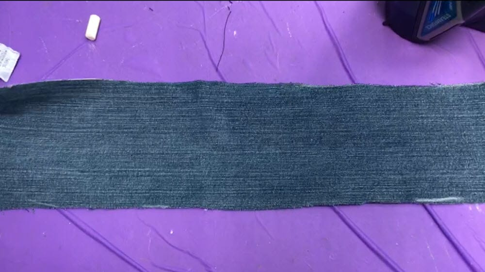Cut strip of jean material for scrunchie on purple background
