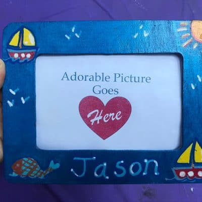 """Hand Holding Metallic Blue Painted Wooden Frame with Sailboat Design and the name """"Jason"""" on it on a purple background"""