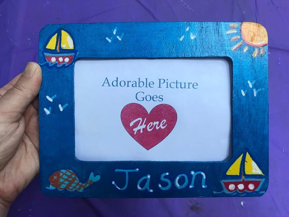 "Hand Holding Metallic Blue Painted Wooden Frame with Sailboat Design and the name ""Jason"" on it on a purple background"