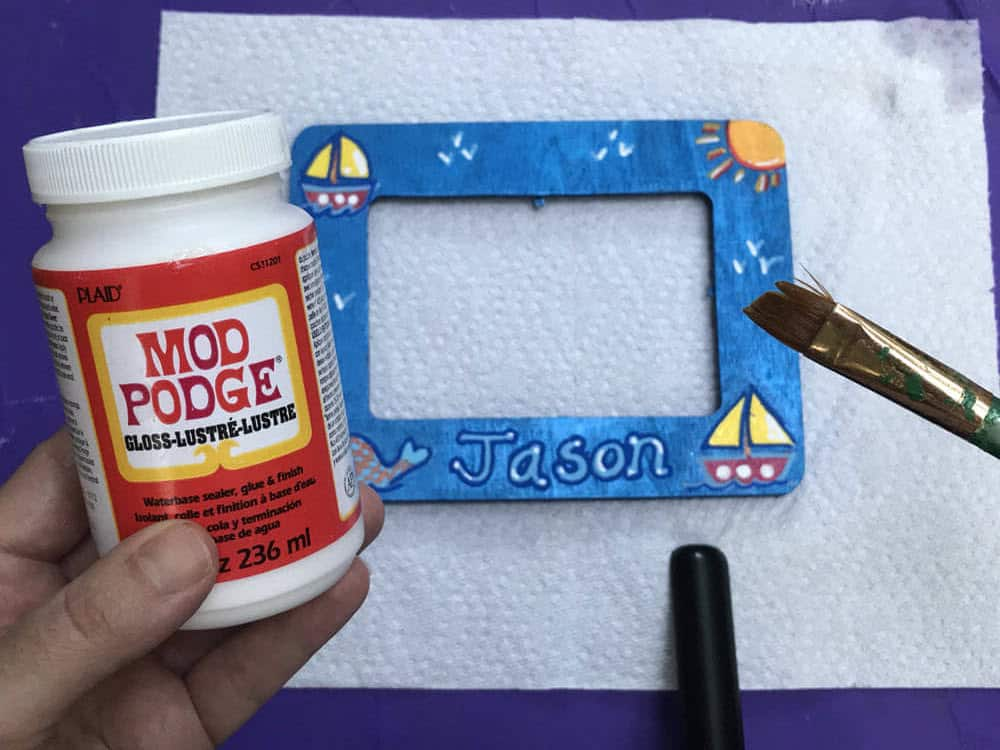 "Hand Holding bottle of Mod Podge in left hand over Blue Painted Frame with sailboat design and the name ""Jason"" a paint brush is also pictured close up on the right"