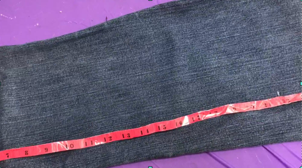 jean material laid out with red tape measure on purple background