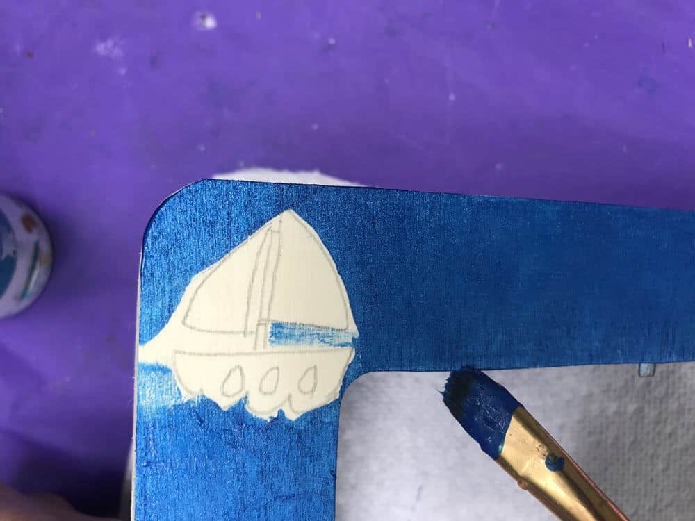 close up of paint brush painting blue background and avoiding pencil design sketches on wooden frame
