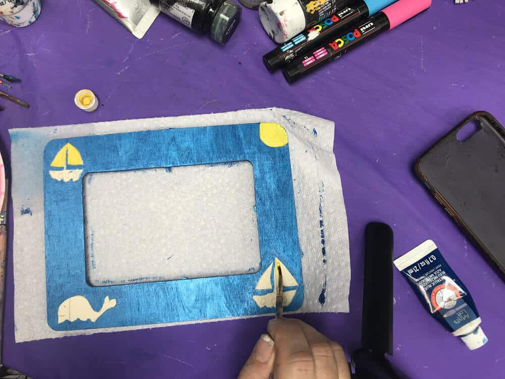Hand Painting Yellow Details unto Painted Wooden Frame with Sailboat Design on Purple background