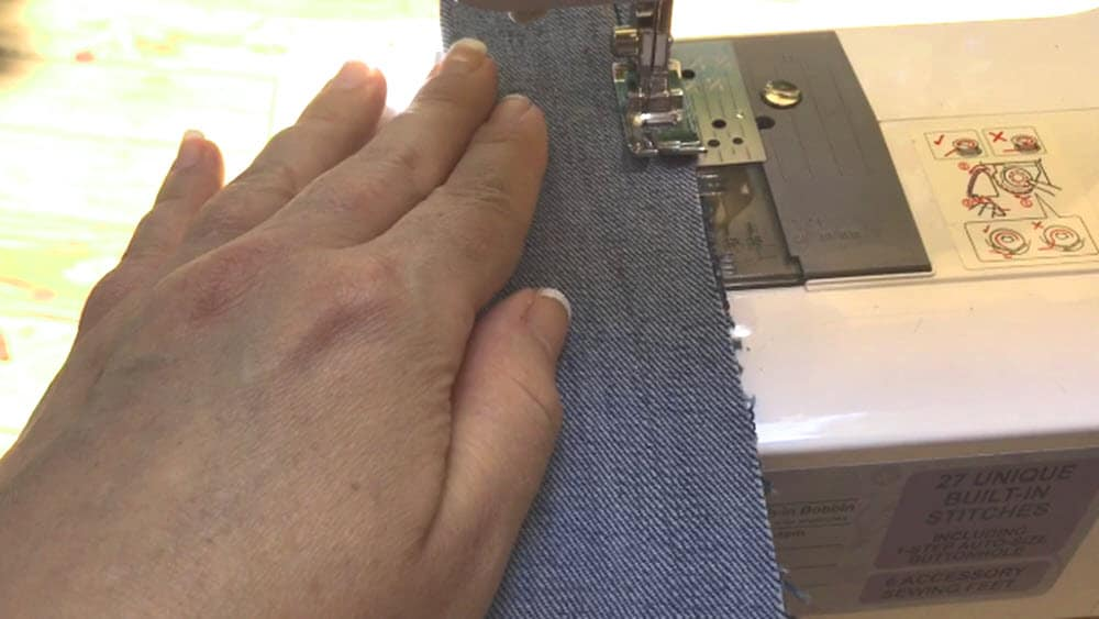 hand guiding jean material through sewing machine for how to make a scrunchie
