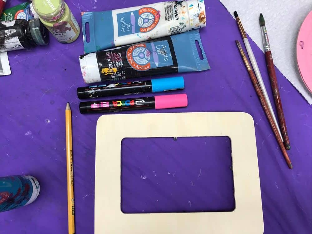 Supplies for DIY Painted Wooden Frame Craft such as Frame, Paint, Paint Brushes, Posca Pens on Purple Background