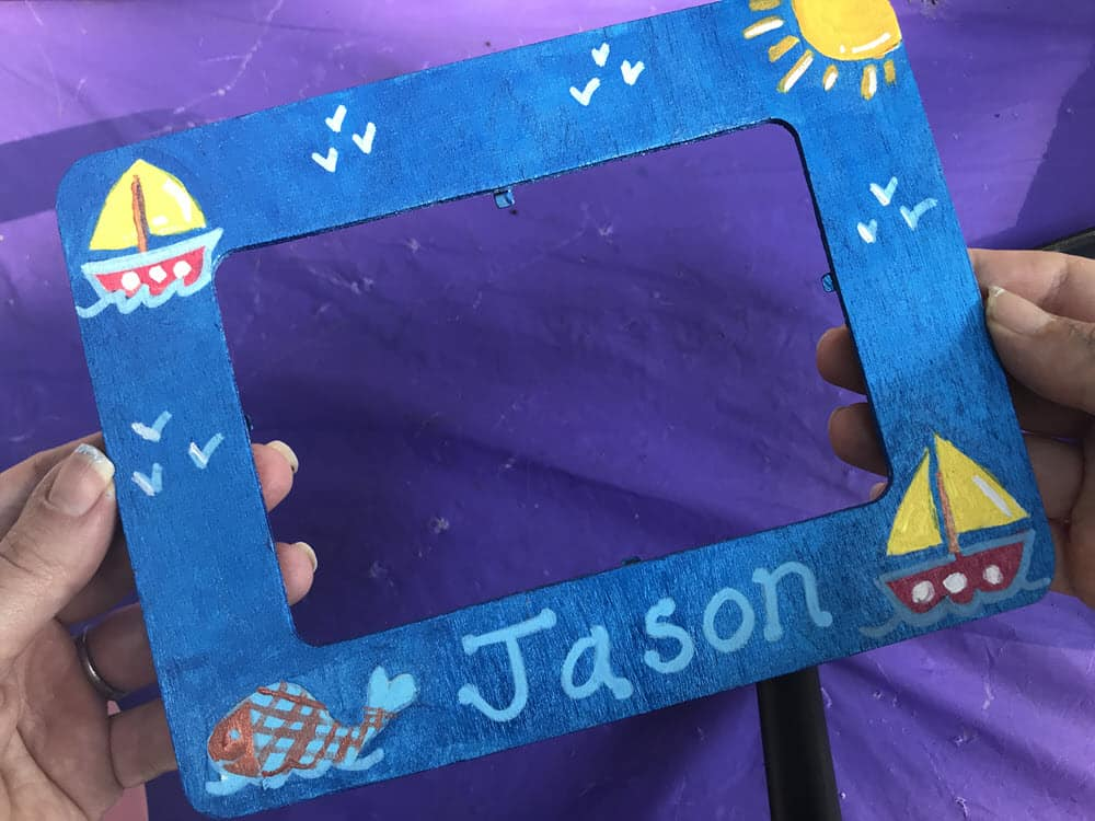 "Two hands holding painted sailboat themed wooden frame with the name ""Jason"" written on it"