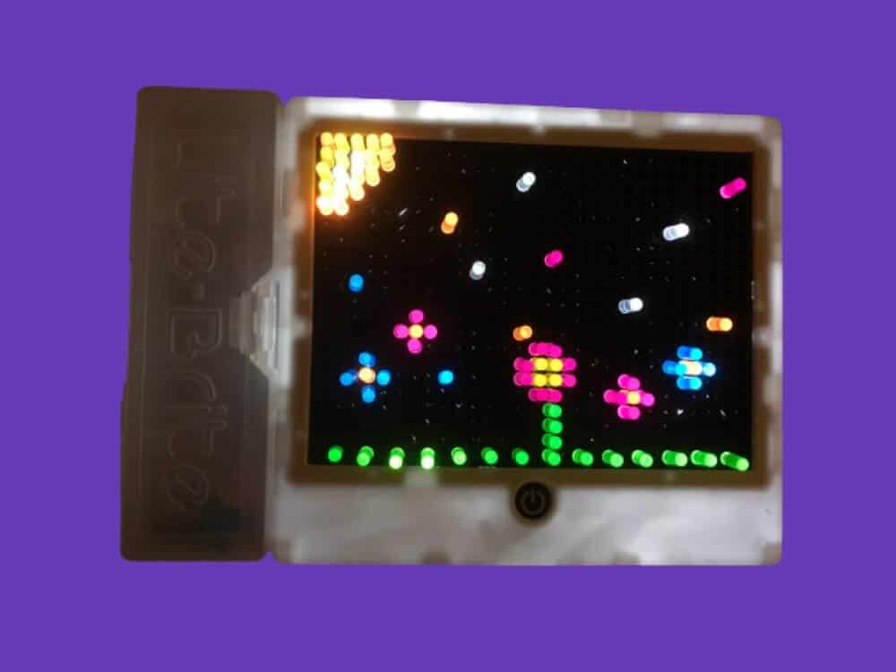 Retro Toy Lite Brite lit up with colorful pegs on a purple background