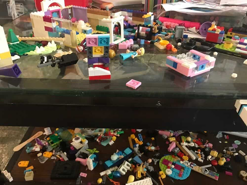 many different lego pieces scattered on to a dark coffee table