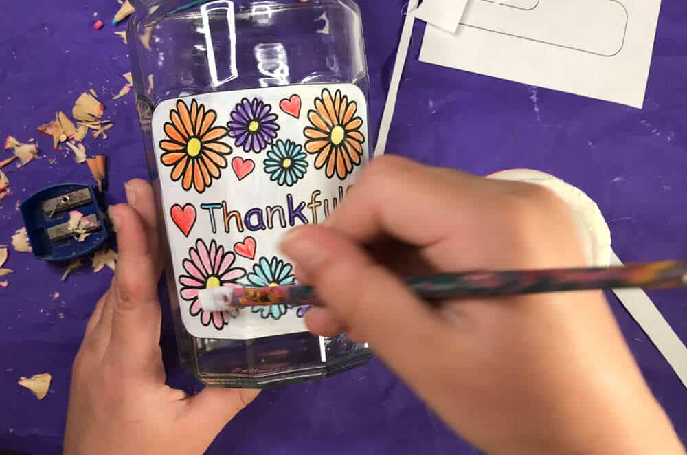 hands applying Mod Podge with a paint brush to Gratitude Jar