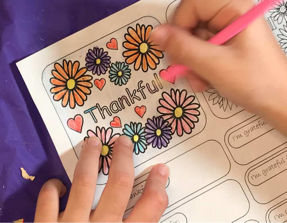 Hands shown coloring Thankful label for Gratitude Jar