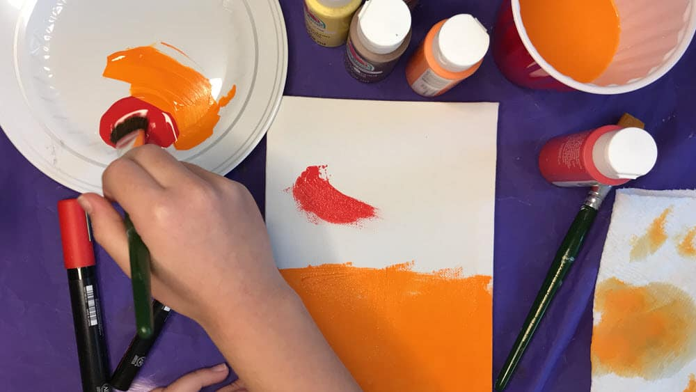 hand painting white canvas with red and orange paint as background color