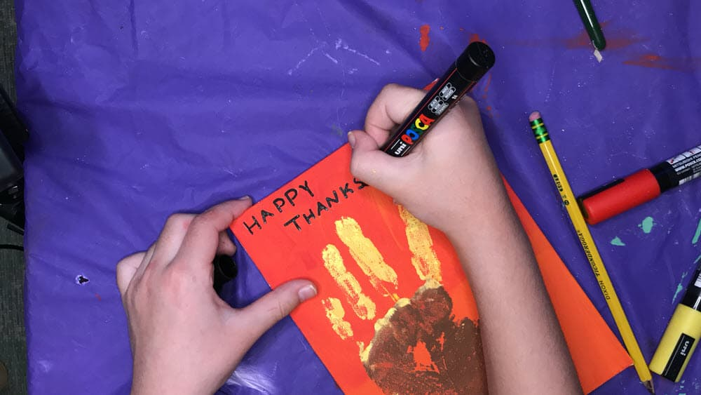Writing Happy Thanksgiving on Turkey Handprint Painting
